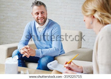 Happy patient talking to psychologist - stock photo