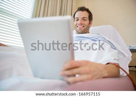 Happy patient using digital tablet during renal dialysis treatment in hospital room - stock photo