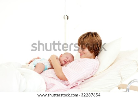 Happy patient with newborn baby in bed in hospital - stock photo