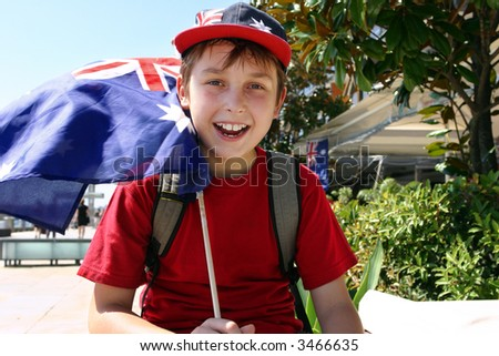Happy patriotic young boy flying a flag on summer national day. - stock photo