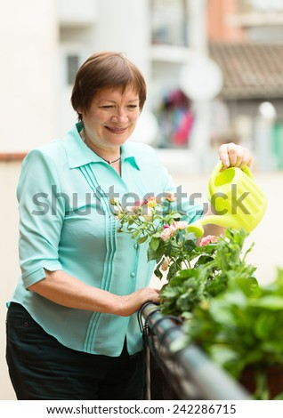 Happy pensioner with watering-can taking care of plants at balcony  - stock photo