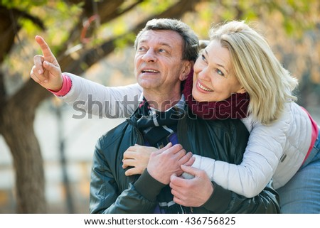 Happy pensioners cuddling in park and enjoying time together - stock photo