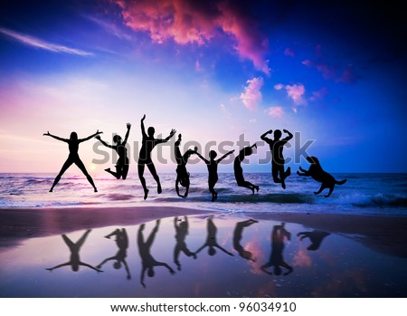 Happy people and dog jumping together on the sunset beach - stock photo