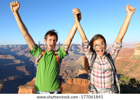 Happy people celebrating cheering in Grand Canyon. Young multiethnic couple on hiking travel excited and elated in Grand Canyon, south rim, Arizona, USA. Asian woman and Caucasian man. - stock photo