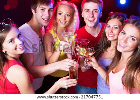 Happy people clinking glasses with each other - stock photo