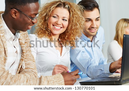 Happy people doing further training in academy course with laptop computer - stock photo