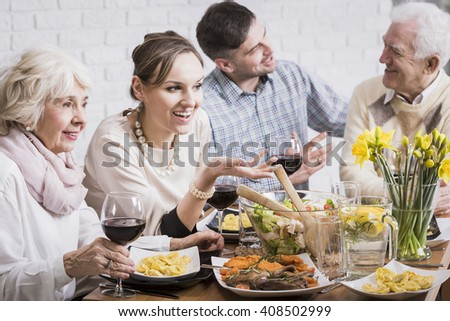 Happy people during family, sunday dinner talking, smiling, drinking red wine