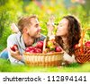 Happy People Eating Healthy Organic Apples in Autumn Garden.Healthy Food.Outdoors.Park.Basket of Apples.Harvest concept .Smiling Couple Relaxing on Grass - stock photo