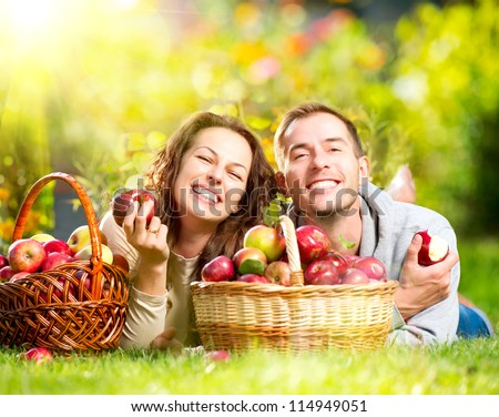 Happy People Eating Organic Apples in Autumn Garden.Healthy Food.Outdoors.Park. Basket of Apples.Harvest concept .Smiling Couple Relaxing on Grass - stock photo