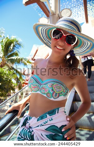 Happy people - glamorous woman in sarong and beautiful summer hat. Cheerful, happiness going to shopping, Hawaii. - stock photo