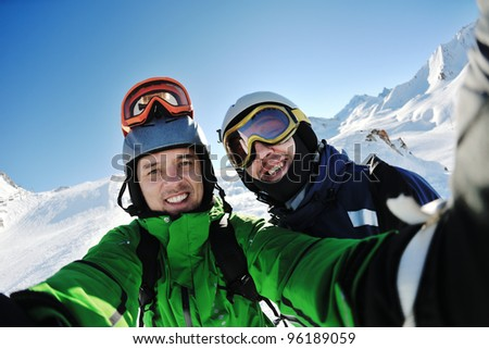 happy people group have fun on ski snow at winter season on mountain with blue sky and fresh air - stock photo
