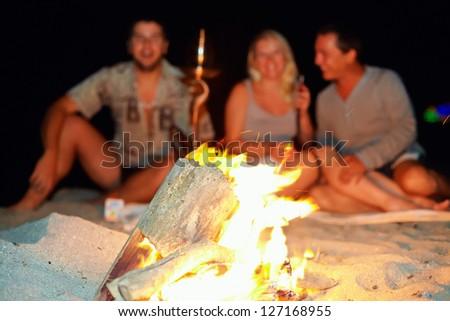 happy people having fun around the bonfire - stock photo
