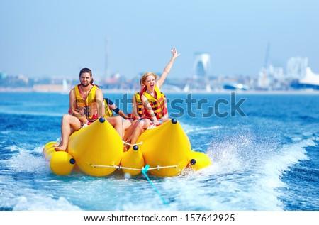 happy people having fun on banana boat - stock photo
