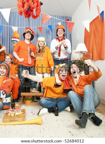 Happy people in a living room seeing their team win an important match - stock photo