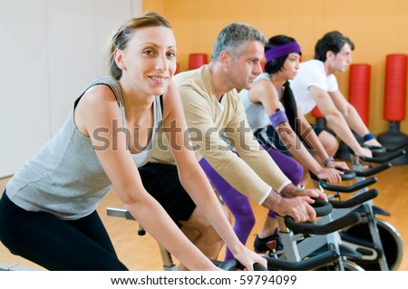 Happy people in a row exercising with bicycles in a gym