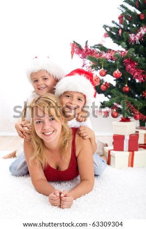Happy people in front of christmas tree playing together - partially isolated - stock photo