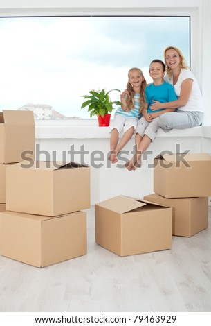 Happy people in their new home among cardboard boxes - sitting on the windowsill with a potted plant - stock photo
