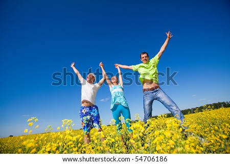 Happy people is jumping in field - stock photo