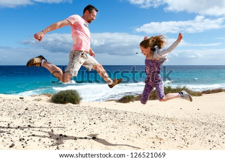 Happy people jumping on a beach. A girl and her father enjoying their vacations - stock photo