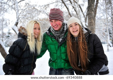Happy people outdoor in winter park enjoying themselves - stock photo