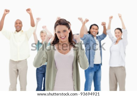 Happy people raising their arms focus on the woman in foreground - stock photo