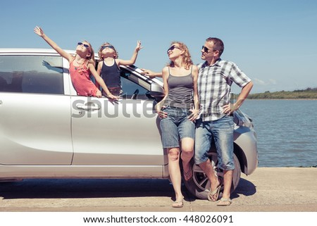 Happy people standing near car. They having fun on the nature.  Concept of friendly family and of summer vacation. - stock photo