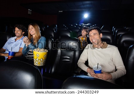 Happy people watching film in movie theater - stock photo