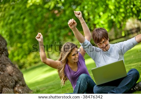 Happy people with laptop computer outdoors - stock photo