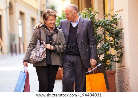 Happy people with senior man and woman shopping and walking with bags in italian city street - stock photo