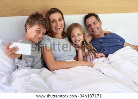 Happy perfect family taking selfie together in bed on weekend smiling and having fun - stock photo