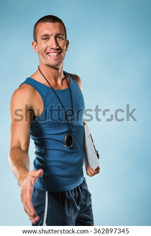 Happy personal trainer giving handshake against blue background - stock photo