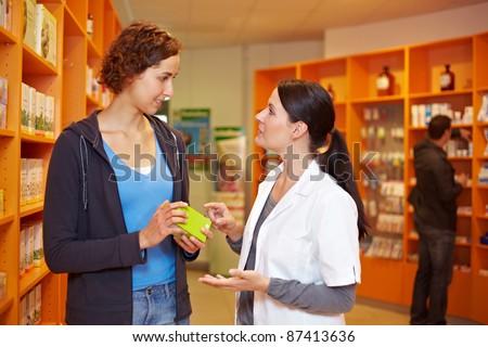 Happy pharmacist advising a woman in a pharmacy - stock photo