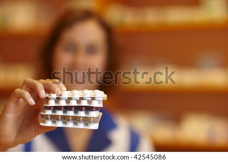 Happy pharmacist holding many pills in hand - stock photo