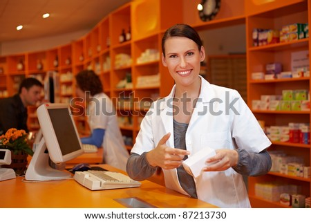 Happy pharmacist in pharmacy pointing to medical product - stock photo