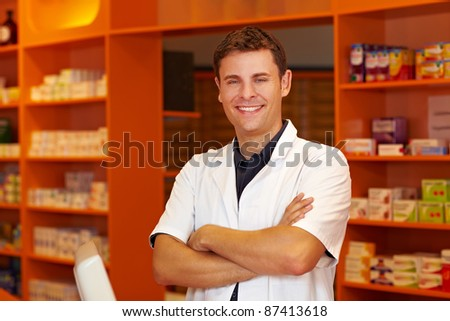 Happy pharmacist in pharmacy with his arms crossed - stock photo