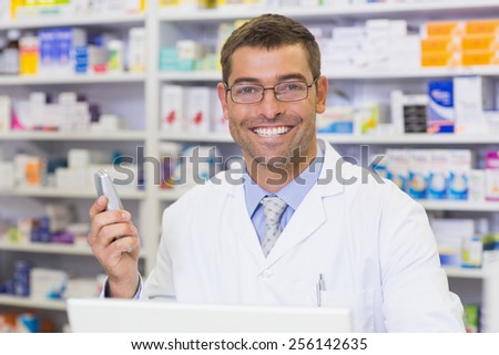 Happy pharmacist on the phone at the hospital pharmacy