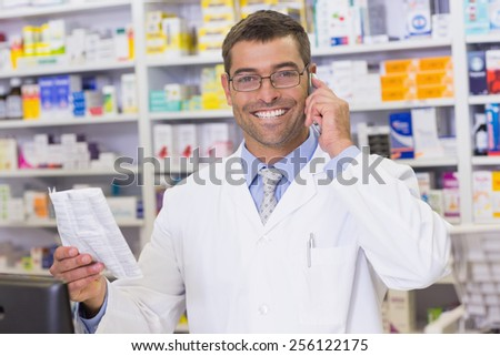 Happy pharmacist on the phone looking at the camera at the hospital pharmacy