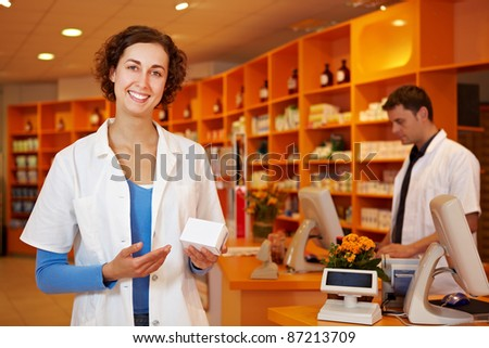 Happy pharmacist recommending a drug in a pharmacy - stock photo