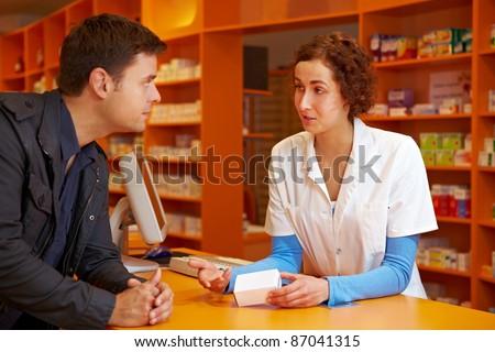 Happy pharmacist talking to customer in a pharmacy - stock photo