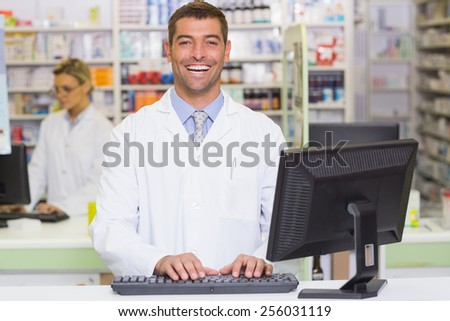 Happy pharmacist using computer at the hospital pharmacy