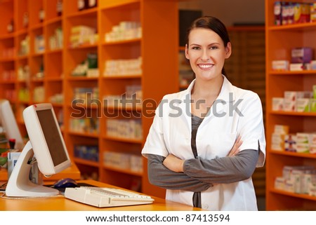 Happy pharmacist with her arms crossed at checkout in pharmacy
