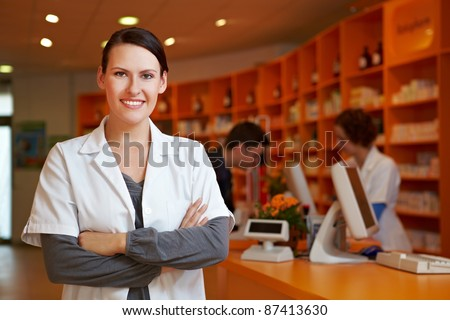 Happy pharmacist with her arms crossed in a pharmacy - stock photo