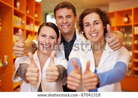 Happy pharmacy team holding their thumbs up in a pharmacy - stock photo