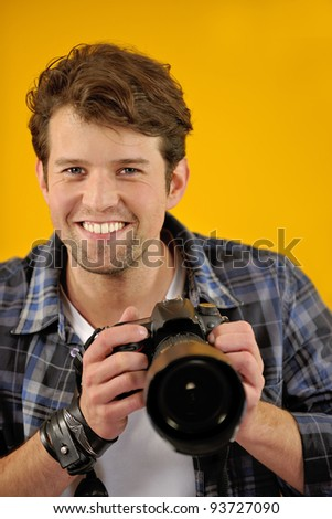 happy photographer with SLR camera on yellow background - stock photo