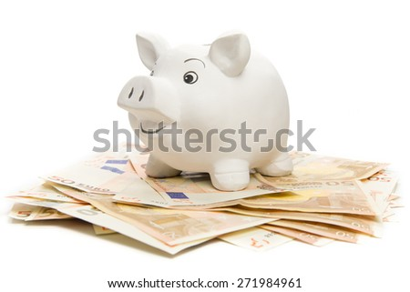 Happy piggy bank on euro banknotes, isolated on white - stock photo
