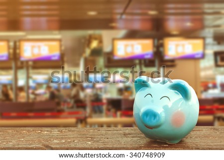 happy piggy bank on wooden floor over airport background ,abstract background to saving money for travel concept - stock photo