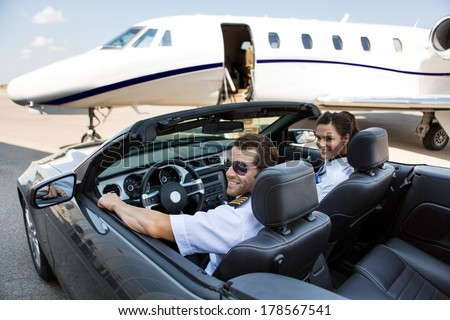 Happy pilot and airhostess in convertible against private jet at terminal - stock photo