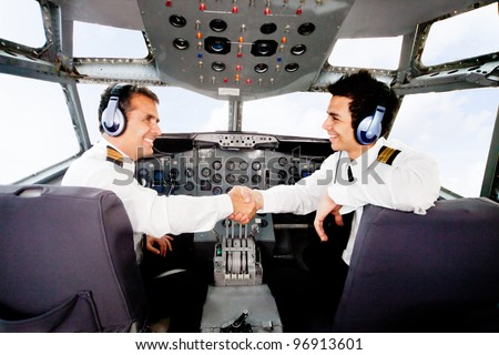 Happy pilots handshaking in the airplane cabin - stock photo