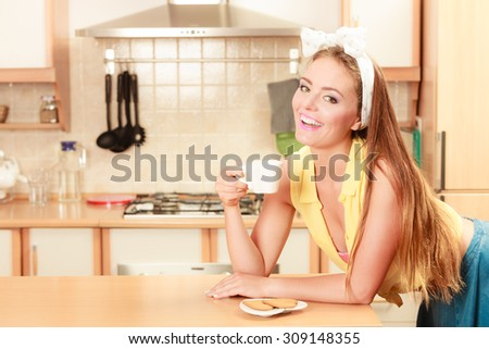 Happy pin up girl with heart shape gingerbread cookies drinking tea or coffee at home. Pretty gorgeous young retro woman with hot beverage relaxing in kitchen.