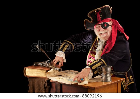 Happy pirate sits at a table with book, quill pen, musket, mug, and torn treasure map. He is wearing a nineteenth century pirate costume with jeweled eye patch. Dark background with copy space. - stock photo